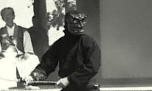 A member of the Bujinkan demonstrating kenjutsu in a demon mask whilst Soke Hatsumi witnesses