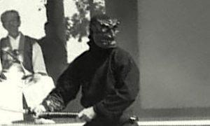 A member of the Bujinkan demonstrating kenjutsu in a demon mask whilst Soke Hatsumi witnesses